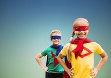 微笑的超级孩子画象在站立用在臀部的手的海角和面具的反对清楚的天空 免版税库存照片