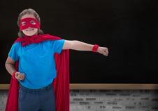 微笑的超级孩子画象在红色海角和红色面具的 免版税库存图片