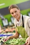 微笑的超级市场雇员在工作 免版税库存照片