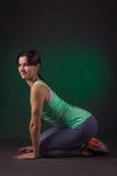 微笑的运动的妇女,健身妇女坐与绿色背后照明的黑暗的背景 库存图片