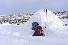 微笑的远足者在冬天时提供一个杯子茶,当坐在一座多雪的小屋园屋顶的小屋 免版税库存图片