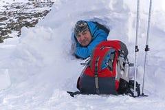 微笑的远足者看在一座多雪的小屋园屋顶的小屋外面在冬天 免版税图库摄影