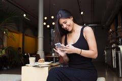 微笑的迷人的拉丁妇女在她的手机读了好消息在caffe大阳台的早餐期间在夏日, 免版税库存照片