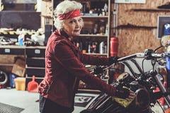 微笑的退休人员擦亮的摩托车在技工商店 免版税图库摄影