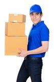 微笑的送货人运载的小包箱子 免版税图库摄影