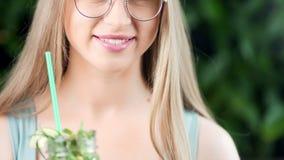微笑的适合的女孩藏品茶点汁饮料的特写镜头性感的嘴唇与秸杆的 股票视频