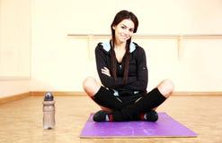 年轻微笑的适合的妇女坐瑜伽席子 免版税库存照片