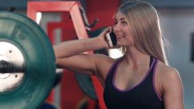 微笑的适合的妇女谈话在电话在健身房举重房 免版税图库摄影