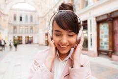 微笑的逗人喜爱的女孩听的音乐的画象与耳机的 免版税库存图片