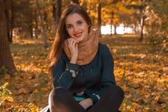 微笑的逗人喜爱的女孩在Scharfe在秋天公园坐 免版税库存照片