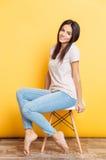 微笑的逗人喜爱的妇女坐椅子 免版税库存图片
