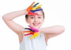 微笑的逗人喜爱的小女孩用被绘的手。 免版税图库摄影