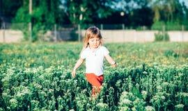 微笑的逗人喜爱的小女孩赛跑 免版税图库摄影