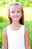 微笑的逗人喜爱的小女孩画象在夏日 免版税库存图片