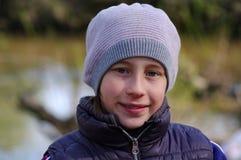 微笑的逗人喜爱的小女孩画象有盖帽的户外在一个春日 图库摄影