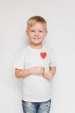 微笑的逗人喜爱的男孩在他的手上的拿着一点纸心脏反对白色背景 免版税库存照片