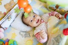 微笑的逗人喜爱的婴孩在卧室 库存图片
