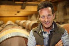 微笑的酿酒商在葡萄酒库里 免版税库存图片
