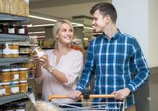 微笑的金发碧眼的女人在超级市场选择与她的丈夫的蜂蜜 库存照片
