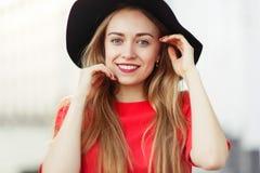 微笑的金发碧眼的女人特写镜头照片红色外套的 免版税库存照片