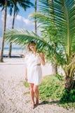 微笑的长发女孩画象有惊人的晒黑佩带的白色礼服的在好的绿色棕榈事假附近 库存照片