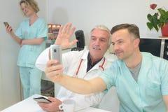 微笑的队医生和护士采取selfie的医院的 库存图片