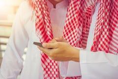 微笑的阿拉伯中东商人画象使用智能手机的 免版税图库摄影