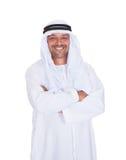 微笑的阿拉伯人常设胳膊横渡了在白色背景 免版税库存照片