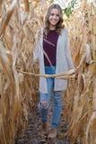 微笑的青少年的女孩在玉米田 免版税库存照片