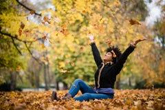 微笑的青少年的女孩投掷的叶子在天空中 免版税库存图片