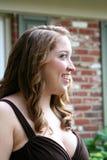 微笑的青少年的女孩在布朗褂子 库存照片