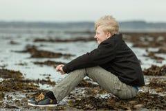 微笑的青少年的男孩坐海滩在低潮期间 免版税库存照片