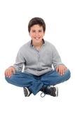 微笑的青春期前的男孩坐地板 图库摄影