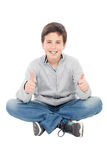 微笑的青春期前的男孩坐说的地板好 库存图片