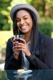 微笑的非洲女孩饮用的茶 库存图片
