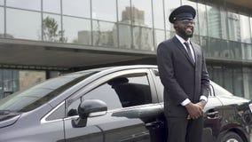 微笑的非裔美国人的出租汽车为期待客户的司机服务在豪华汽车附近 影视素材