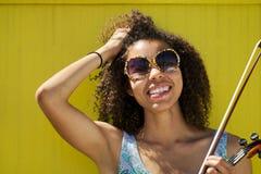 微笑的非裔美国人的妇女用在头发的手 免版税图库摄影
