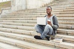 微笑的非裔美国人的学生坐台阶用咖啡使用膝上型计算机 库存照片