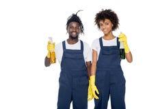 微笑的非裔美国人的擦净人画象橡胶手套的与洗涤剂在看照相机的手上 免版税库存图片