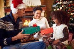微笑的非裔美国人的父母给被点燃的圣诞节礼物他们 免版税图库摄影