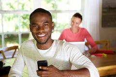 微笑的非洲人在家有使用膝上型计算机的妇女的在背景 免版税图库摄影