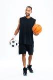 微笑的非洲体育供以人员拿着篮球和足球 免版税库存图片