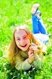 微笑的面孔的女孩拿着红色郁金香花,享受芳香 说谎在草,在背景的grassplot的女孩 青年时期和 免版税库存图片