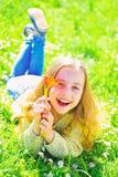 微笑的面孔的女孩拿着红色郁金香花,享受芳香 说谎在草,在背景的grassplot的女孩 青年时期和 免版税图库摄影