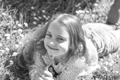 微笑的面孔的女孩拿着红色郁金香花,享受芳香 青年时期和无忧无虑的概念 孩子享受春天好日子一会儿 图库摄影