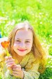 微笑的面孔的女孩拿着红色郁金香花,享受芳香 青年时期和无忧无虑的概念 说谎在草,grassplot的女孩  免版税图库摄影