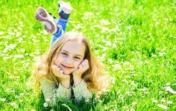 微笑的面孔的女孩花费休闲户外 全盛时期概念 孩子享受春天晴朗的天气,当说谎在草甸时 免版税库存照片