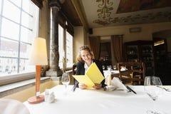 微笑的顾客读书菜单在餐馆桌上 免版税库存照片