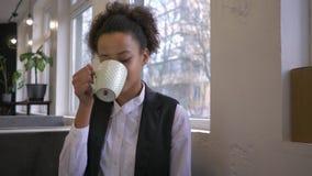微笑的黑人女孩做使与茶的叮当声叮当响与朋友的在咖啡馆 股票录像