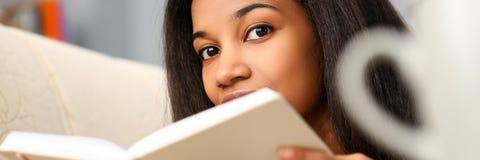 微笑的黑人妇女在家读了故事书 免版税库存图片
